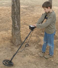 attractions-for-road-trip-06; boy using metal detector to hunt for treasure
