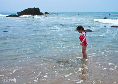 my daughter standing in the waves