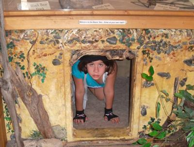 Sara in a bear cave exhibit