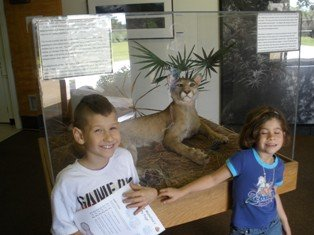 William and Sara in front of a bobcat