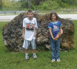 Outside, braving the bugs, at a big rock (not too happy)